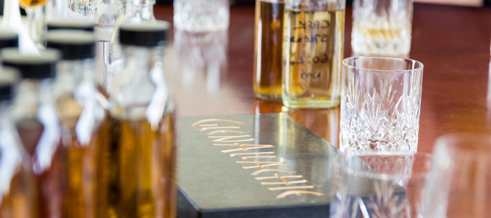 Nahaufnahme Steinblock mit GlenAllachie Aufschrift, Probeflaschen und Gläser
